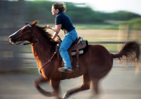 Barrel rider races her horse in practice, Indian Head Saskatchewan Canada - Photo by David Innes
