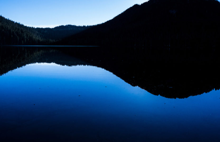 Clear blue sky is reflected in the deeper blue still water of Lake Helen McKenzie,in Strathcona Provincial Park, Vancouver Island BC Canada at dusk. A backlit rolling black treeline is silhouetted in the upper half of the image, with the blue of the sky above and the deeper blue hue of the lake below. - Photo by David Innes