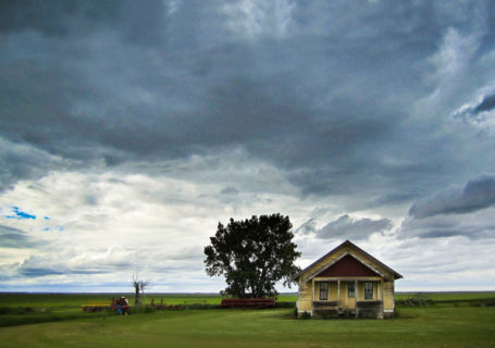 Abandoned farmhouse sits on a flat horizon, menacing storm clouds overhead, Saskatchewan - Photo by David Innes