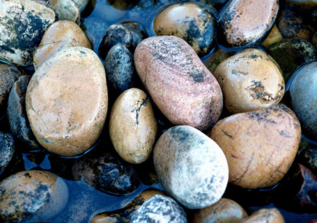 Water softly flows over creek stones - Photo by David Innes